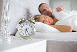Exhausted couple looking at alarm clock