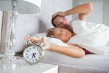 Tired couple looking at alarm clock in the morning with woman turning it off
