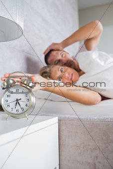Annoyed couple looking at alarm clock in the morning with woman turning it off