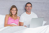 Attractive young couple using their laptop together in bed
