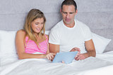 Attractive young couple using their tablet pc together in bed