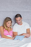 Cute young couple using their tablet pc together in bed
