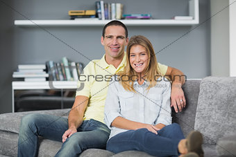 Attractive young couple sitting on their couch