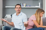 Couple sitting back to back after a fight on the couch with man gesturing at camera