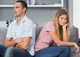 Couple sitting back to back after a fight on the couch with woman looking at camera