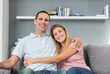 Couple sitting on the couch smiling at camera