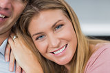 Happy couple sitting on the couch smiling at camera focus on woman