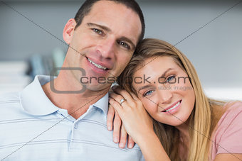 Attractive couple sitting on the couch smiling at camera
