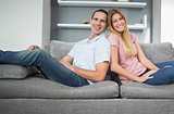 Relaxed couple sitting back to back on the couch together