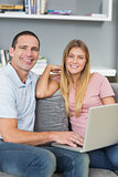Cheerful couple sitting using laptop on the couch together