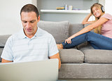 Man sitting on floor with laptop with woman listening to music on the couch