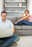 Man sitting on floor using laptop with woman listening to music on the sofa