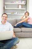 Man sitting on floor using laptop with woman listening to music on the sofa both smiling at camera