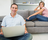 Man sitting on floor using laptop with woman listening to music on the sofa both looking at camera