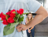 Man hiding bouquet of roses from girlfriend on the couch