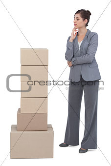 Thoughtful businesswoman with cardboard boxes