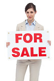 Businesswoman with for sale sign