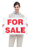 Smiling businesswoman with for sale sign