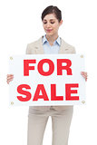 Estate agent holding for sale sign