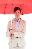 Cheerful young businesswoman with red umbrella