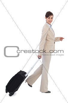 Cheerful businesswoman pulling suitcase