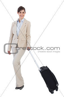 Happy businesswoman posing with suitcase