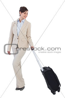 Classy businesswoman posing with suitcase