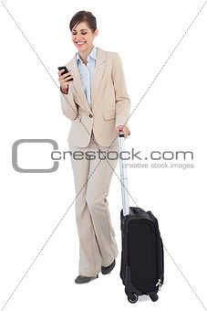 Cheerful businesswoman with suitcase and phone