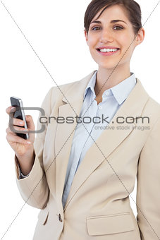 Cheerful businesswoman posing with phone on right hand