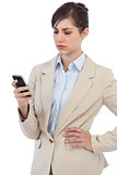 Serious businesswoman posing with phone on right hand