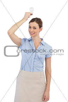 Businesswoman holding a light bulb above her head