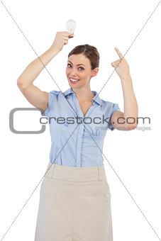 Classy businesswoman holding light bulb above her head