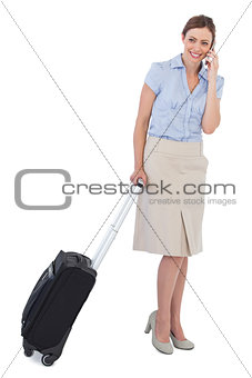 Cheerful classy businesswoman with suitcase and phone
