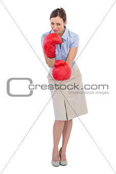 Attractive businesswoman posing with red boxing gloves