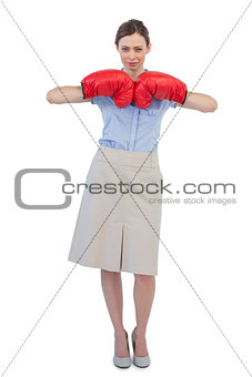 Tough businesswoman posing with red boxing gloves