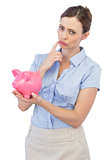Thoughtful businesswoman with piggy bank