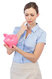 Pensive businesswoman with piggy bank