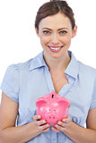 Pretty businesswoman holding piggy bank