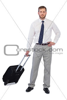 Serious handsome businessman with suitcase