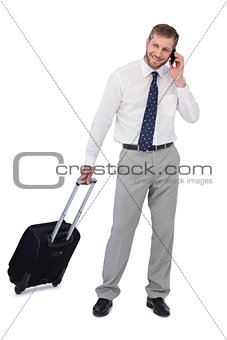 Handsome businessman with suitcase and phone