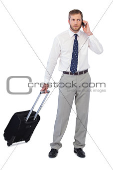 Handsome businessman posing with suitcase and phone