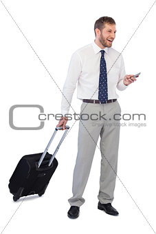 Wide smiling businessman with phone and suitcase