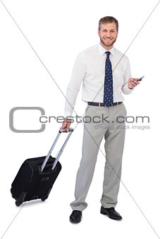 Businessman with phone and suitcase looking at camera