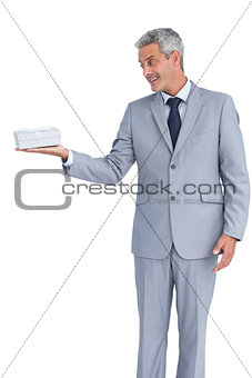 Handsome businessman holding gift on right hand