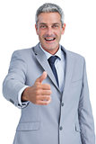 Cheerful businessman looking at camera reaching for handshake