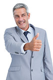 Cheerful businessman reaching for handshake
