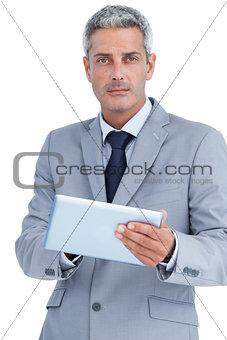 Serious businessman using digital tablet
