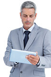 Frowning businessman using digital tablet