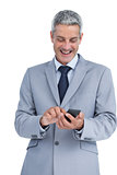 Happy businessman sending text message