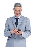 Happy businessman sending text message